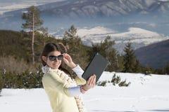 Маленькая девочка делает фото selfie с таблеткой в зиме Стоковые Фото
