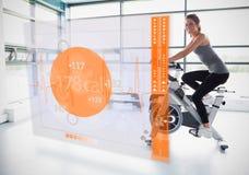 Маленькая девочка делая велотренажер при футуристический интерфейс показывая калории стоковая фотография rf