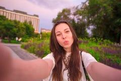 Маленькая девочка делая видео- selfie и имея потеху в парке Портрет selfie образа жизни молодой положительной женщины имея потеху Стоковая Фотография