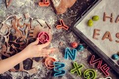 Маленькая девочка делая печенья пасхи Стоковые Изображения