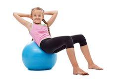 Маленькая девочка делая подбрюшные гимнастические тренировки стоковые фотографии rf