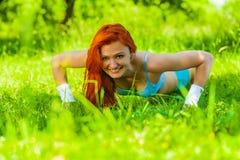 Маленькая девочка делая прессу поднимает на траве Стоковые Изображения RF