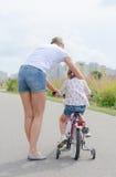 Маленькая девочка женщины уча, который нужно ехать Стоковое Фото