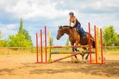 Маленькая девочка жокея делая лошадь скача через барьер Стоковое Изображение RF