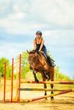 Маленькая девочка жокея делая лошадь скача через барьер стоковые изображения rf