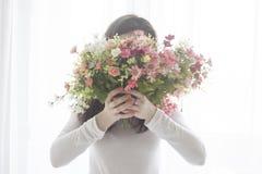 Маленькая девочка закрыла сторону при букет цветков, изолированный на белой предпосылке Стоковая Фотография