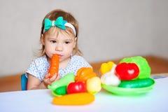 Маленькая девочка играет на таблице с овощами Вегетарианец ребенка Принципиальная схема здоровой еды Стоковое Изображение