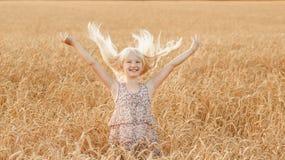 Маленькая девочка играет с ее волосами в поле с пшеницей Стоковые Изображения