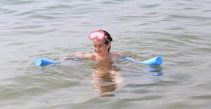 Маленькая девочка играет с плавая пластичной трубкой и ныряя маской Стоковая Фотография RF
