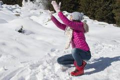 Маленькая девочка играет с снегом в зиме Стоковые Фотографии RF