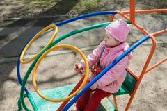 Маленькая девочка играя внутренний вертолет бара обезьяны на внешней спортивной площадке Стоковое Изображение