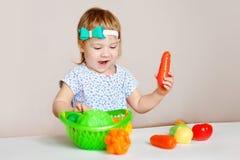 Маленькая девочка играя внутри помещения дома или детский сад Прелестные усмехаясь овощи пластмассы вырезывания маленького ребенк Стоковое Изображение
