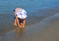 Маленькая девочка играя в воде на пляже Стоковые Фотографии RF