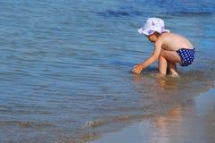 Маленькая девочка играя в воде на пляже Стоковое Изображение