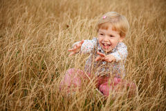 Маленькая девочка играя в траве Стоковое Фото