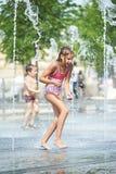 Маленькая девочка играя в фонтане Стоковая Фотография