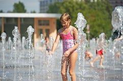 Маленькая девочка играя в фонтане Стоковые Изображения