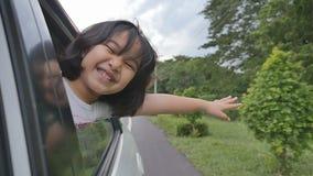 Маленькая девочка играя на автомобиле окна, семья путешествуя на сельской местности сток-видео