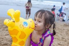 Маленькая девочка играя на пляже целуя жирафа игрушки Стоковое Изображение RF
