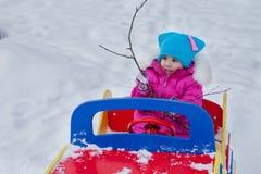 Маленькая девочка играя на спортивной площадке, имеющ потеху играя закручивающ день зимы на улице в парке Стоковое Фото
