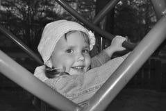 Маленькая девочка играя на спортивной площадке и смехе. Стоковые Изображения