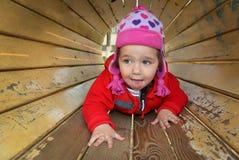 Маленькая девочка играя на спортивной площадке Стоковые Изображения RF
