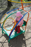 Маленькая девочка играя регулирующ вертолет бара обезьяны игры на внешней спортивной площадке Стоковое Фото