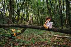 Маленькая девочка играя с ее медведем в древесинах девушка сидя дальше Стоковая Фотография