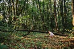 Маленькая девочка играя с ее медведем в древесинах девушка сидя дальше Стоковые Фотографии RF