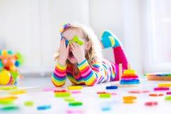 Маленькая девочка играя с деревянными игрушками Стоковое Фото