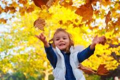 Маленькая девочка играя с листьями стоковые изображения rf