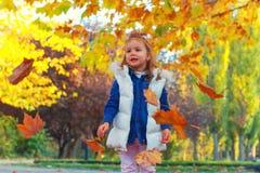 Маленькая девочка играя с листьями стоковая фотография rf
