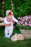 Маленькая девочка играя с кроликом на траве стоковое фото rf