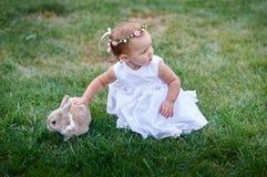 Маленькая девочка играя с кроликом на траве стоковое фото