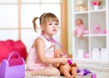Маленькая девочка играя с куклами в больнице Стоковое Фото