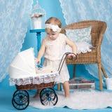 Маленькая девочка играя с куклами и прогулочной коляской Стоковые Изображения RF