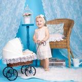 Маленькая девочка играя с куклами и прогулочной коляской Стоковое Изображение RF