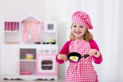 Маленькая девочка играя с кухней игрушки Стоковые Изображения RF