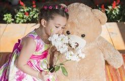 Маленькая девочка играя с медведем игрушки снаружи Стоковое Фото