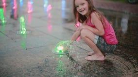 Маленькая девочка играя с покрашенными струями воды на фонтане Подача с ее рукой, стойки ребенка касающая на струе воды видеоматериал
