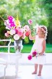 Маленькая девочка играя с свежими цветками Стоковое фото RF