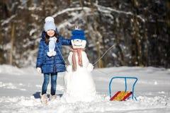 Маленькая девочка играя с снеговиком Стоковая Фотография