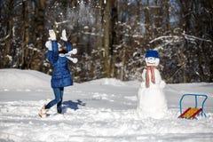 Маленькая девочка играя с снеговиком Стоковое Фото