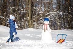 Маленькая девочка играя с снеговиком Стоковое Изображение