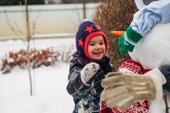 Маленькая девочка играя с снеговиком Стоковая Фотография RF