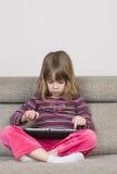 Маленькая девочка играя с цифровой таблеткой Стоковое Изображение