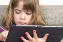Маленькая девочка играя с цифровой таблеткой Стоковое Изображение RF