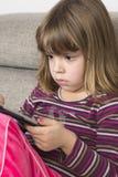 Маленькая девочка играя с цифровой таблеткой Стоковое фото RF