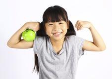 Маленькая девочка изгибает ее мышцу пока показывающ яблоко Стоковое фото RF