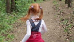 Маленькая девочка имбиря бежать через древесины видеоматериал